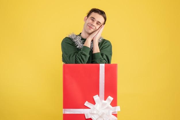 Vista frontale assonnato giovane uomo in piedi dietro grande giftbox su giallo