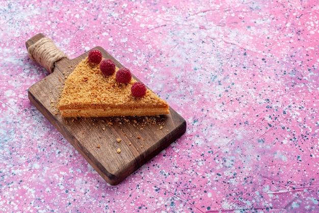 明るいピンクの机の上にラズベリーと一緒に焼いて甘いケーキの正面スライスは甘いケーキパイを焼く