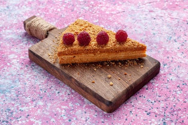 明るいピンクの机の上でラズベリーと一緒に焼いて甘いケーキの正面スライスは甘いケーキパイフルーツを焼く