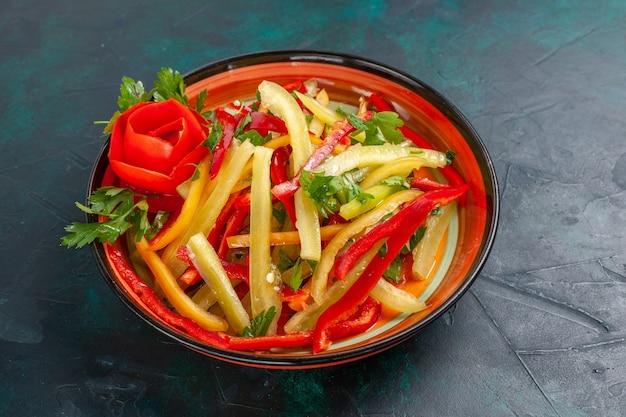 Вид спереди нарезанный болгарский перец салат разного цвета внутри тарелки на темной поверхности