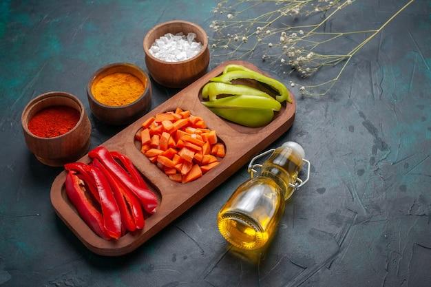 紺色の表面に調味料とオリーブオイルを添えたスライスしたピーマンの正面図