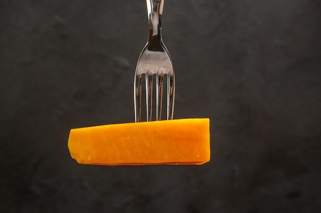 Vista frontale del formaggio a fette sulla forchetta su un pasto scuro foto a colori colazione croccante