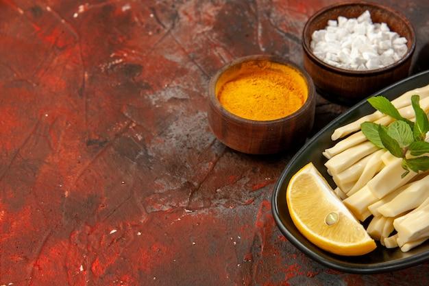 正面図スライスチーズとレモンピースと調味料を暗い食事の食べ物スナック写真の色のない場所に