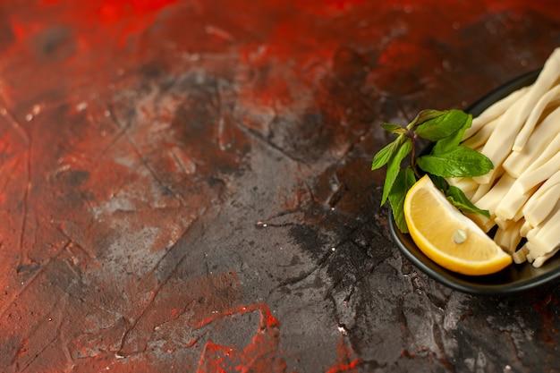 Formaggio a fette vista frontale con pezzo di limone all'interno del piatto su pasto scuro snack frutta colore foto cibo posto libero