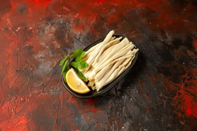 暗い食事スナック フード カラー フルーツの写真のプレートの内側にレモンの部分とスライス チーズの正面図