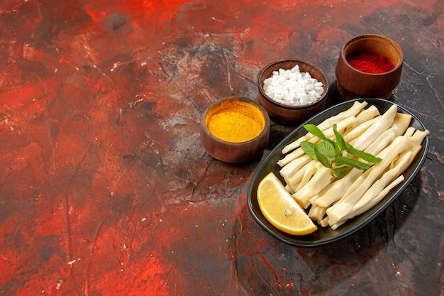 Formaggio a fette vista frontale con pezzo di limone e condimenti su cibo scuro snack foto a colori spazio libero