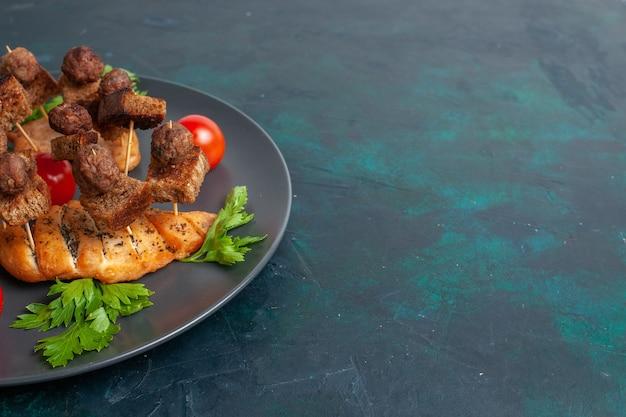 Вид спереди нарезанное приготовленное мясо с зеленью помидоров черри внутри тарелки на темно-синей поверхности