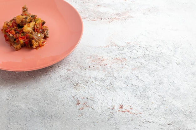 Vista frontale affettata di carne cotta con salsa all'interno della piastra sulla superficie bianca