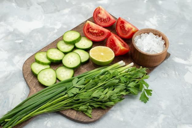 Вид спереди нарезанные огурцы и помидоры с соленой зеленью и лимоном на белом, салат овощной зелени