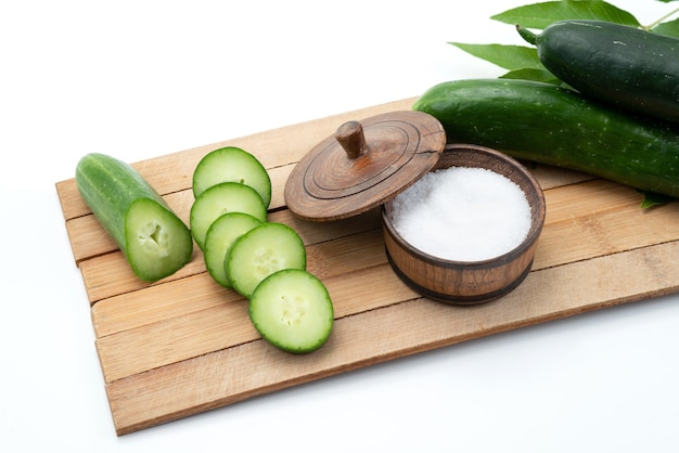 A front view sliced cucumbers with whole cucumbers and salt on brown wooden desk and white food meal