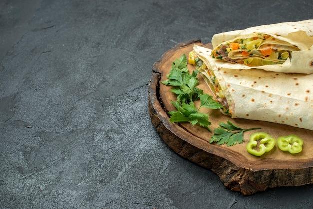 正面図スライスしたおいしいシャワルマサラダサンドイッチダークグレーの表面の食事サラダハンバーガーサンドイッチ食品