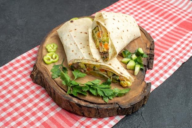 正面図スライスしたおいしいシャワルマサラダサンドイッチと緑の灰色の表面の食事ピタサラダサンドイッチバーガー