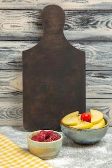 Вид спереди нарезанные свежие яблоки с малиной на сером фоне спелых спелых фруктов