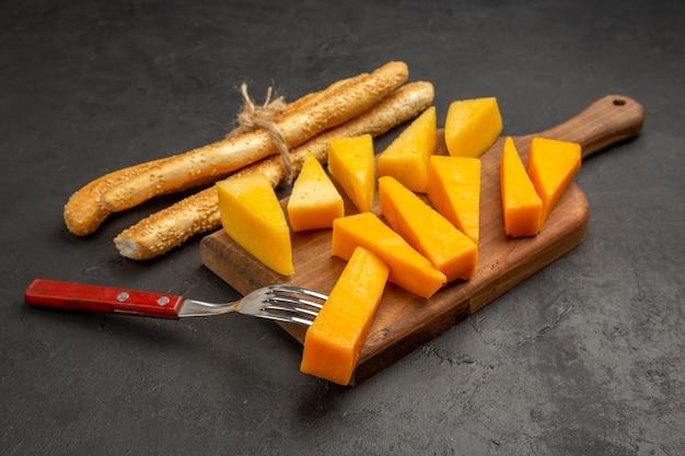 Вид спереди нарезанный свежий сыр с булочками на темной фотографии закуски цветные чипсы для завтрака