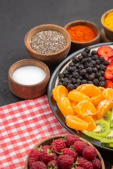 Vista frontale di frutta fresca affettata con condimenti su insalata di colore scuro frutta dolce matura