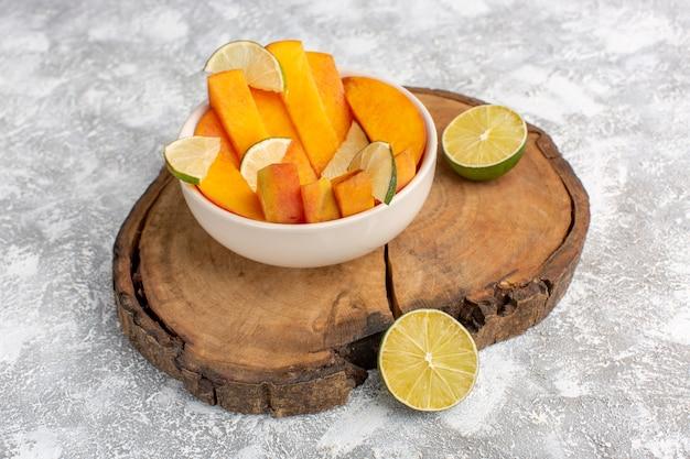 Vista frontale di pesche fresche a fette all'interno del piatto con limoni su sfondo bianco chiaro.