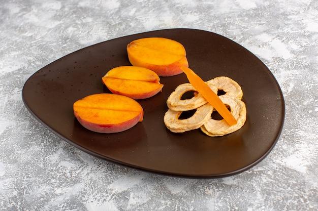 Pesche fresche affettate vista frontale all'interno del piatto con anelli di ananas sulla scrivania bianca chiara.