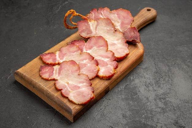 木製の机の上にハムをスライスし、グレーの写真の色の肉料理の生豚を正面から見た図
