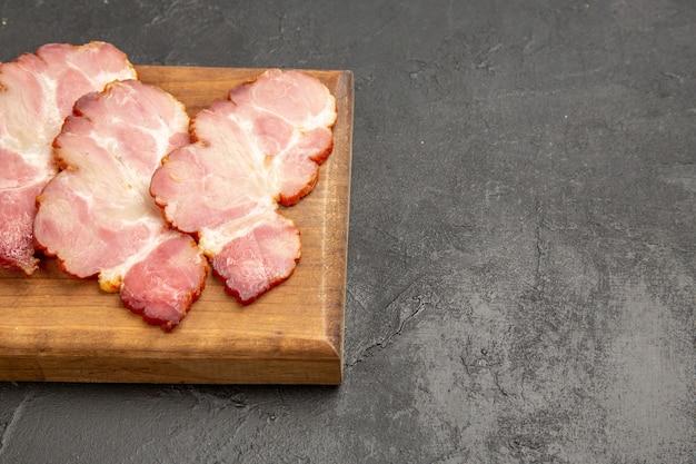 木製の机の上にハムをスライスした正面図とグレーの写真の肉料理の食事生の豚