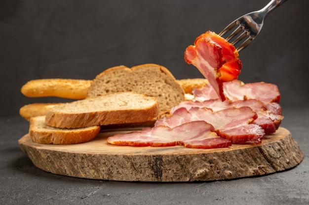 Prosciutto affettato vista frontale con fette di pane sul colore del maiale alimentare per spuntino a base di carne grigio scuro