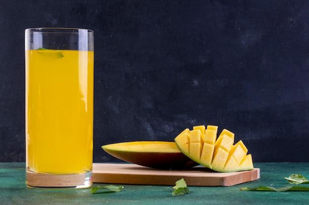 Mango affettato vista frontale su una lavagna con un bicchiere di succo d'arancia