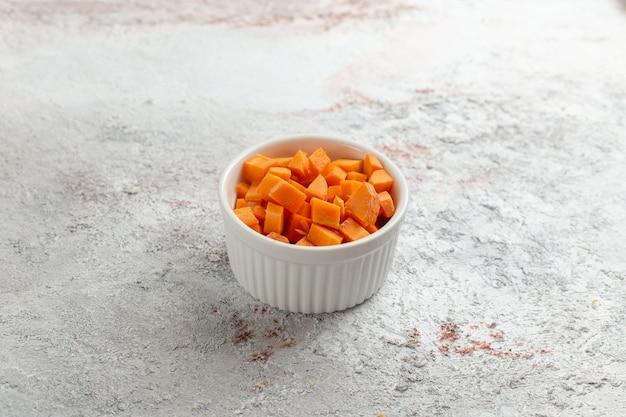 白い表面の小さな鍋の中にスライスしたオレンジ色の野菜の正面図