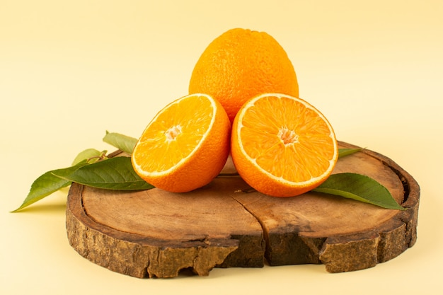 A front view sliced orange and whole with green leaves on the wooden brown desk isolated fresh juicy mellow on the cream