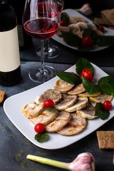 Una vista frontale ha affettato il patè dentro il piatto bianco insieme alle patatine fritte del vino rosso delle foglie verdi sul pasto grigio della cena dello scrittorio