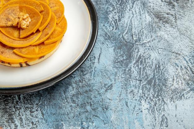 Vista frontale del cachi a fette con pancake sulla superficie chiara