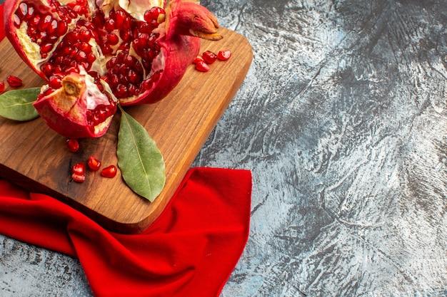 正面図スライスしたザクロの新鮮な赤い果実を明暗の床に新鮮な赤い果実