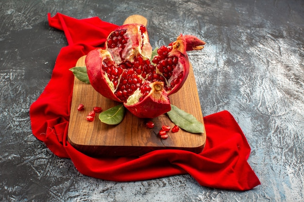 正面図スライスしたザクロの新鮮な赤い果物を明暗のテーブルに置いた果物赤い新鮮