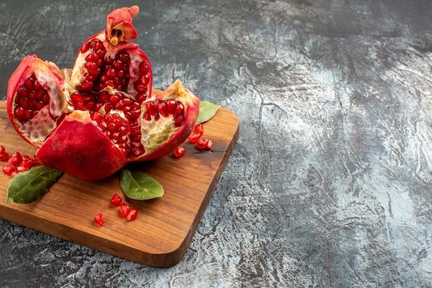 Вид спереди нарезанные гранаты свежие красные фрукты на светлом столе