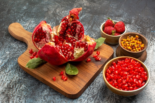 ライトテーブルカラーの新鮮な果物に他の果物と一緒にスライスしたザクロの正面図