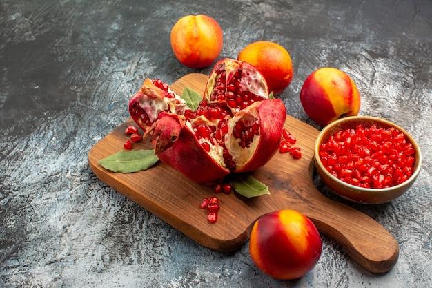 暗いテーブルの果樹の新鮮な色に桃とスライスしたザクロの正面図