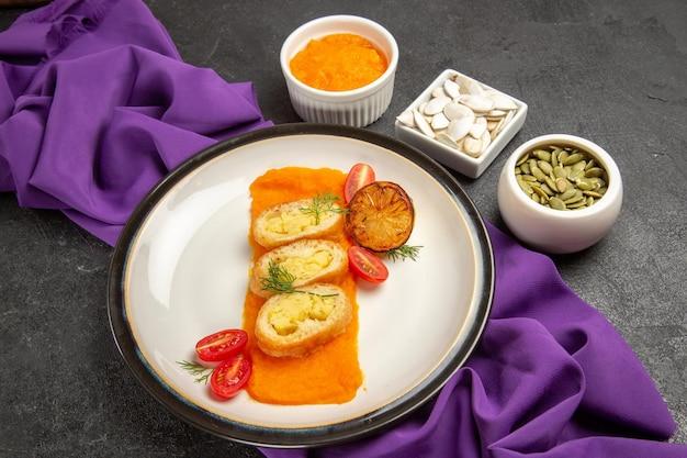 灰色の背景にマッシュポテトとトマトのスライスしたポテトパイの正面図オーブンケーキパイ焼き色