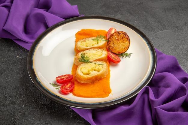 Torte di patate affettate vista frontale con purè di zucca e pomodori sullo sfondo grigio