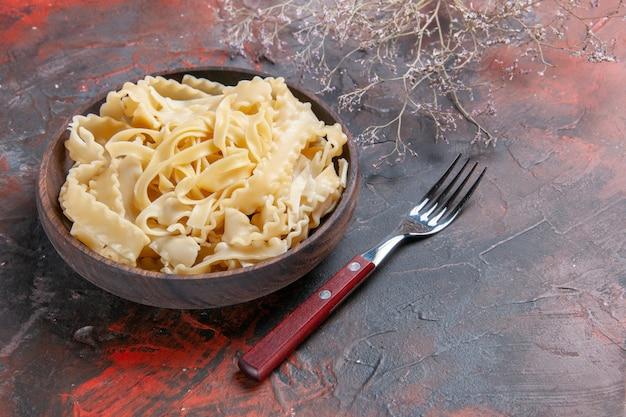 Вид спереди нарезанное сырое тесто внутри тарелки на темной поверхности темное тесто, макароны, еда в сыром виде