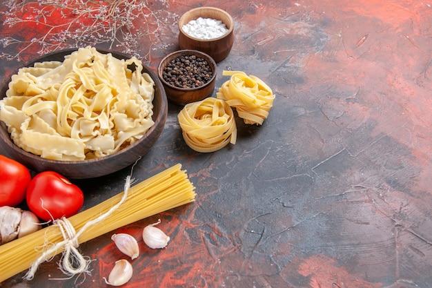 Vista frontale a fette di pasta cruda con condimenti sulla superficie scura pasta pasta cibo scuro