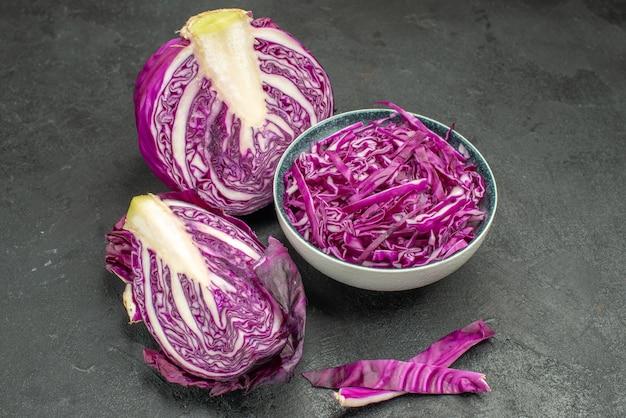 暗いテーブルの上にスライスした赤キャベツの新鮮な野菜の正面図