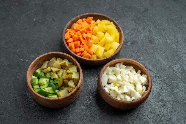 暗い表面のサラダランチスナック野菜の鍋の中のスライスされたサラダ材料の正面図