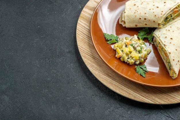 正面図スライスしたシャワルマのおいしい肉と灰色の表面のサラダサンドイッチハンバーガーサンドイッチパンピタ肉