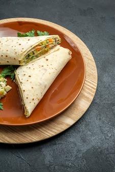 Vista frontale shaurma affettato carne gustosa e panino con insalata su superficie grigia panino con hamburger insalata pane pita carne