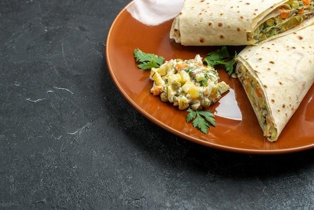 正面図スライスしたシャワルマおいしい肉サンドイッチ、ダークデスクのプレート内ハンバーガーサンドイッチパンピタ肉