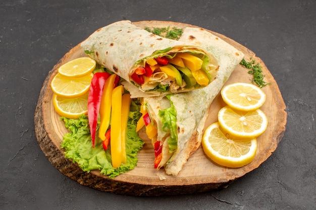 Вид спереди нарезанный шаурма вкусный мясной сэндвич с ломтиками лимона на темном пространстве