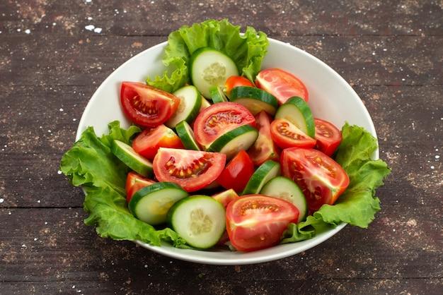 Вид спереди нарезанные помидоры с огурцами внутри белой тарелке с зеленым салатом на коричневом, еда овощная свежий обед салат