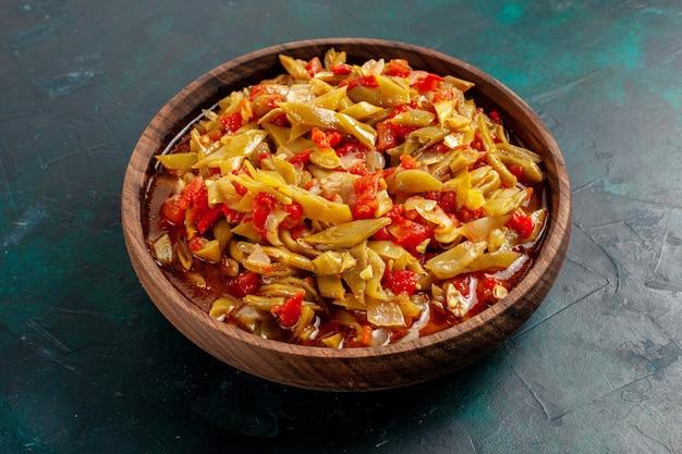 Нарезанная овощная еда, приготовленная с разными ингредиентами на синей поверхности, вид спереди