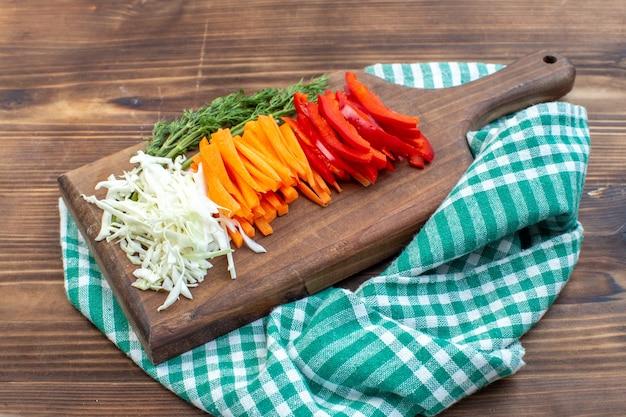 まな板の茶色の表面にスライスした野菜キャベツにんじんグリーンとコショウの正面図