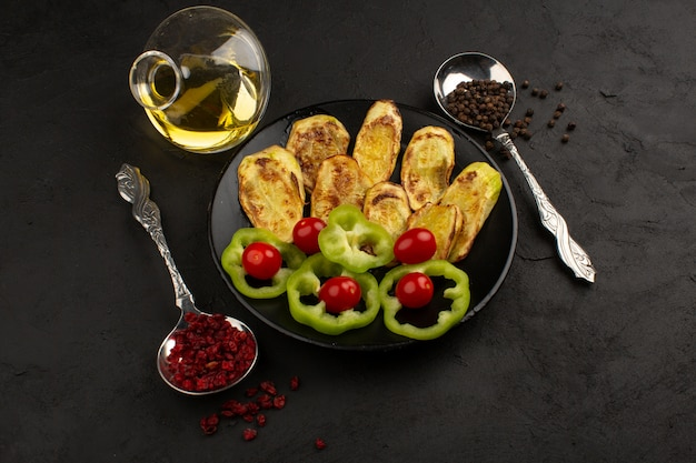 緑のピーマンなどのカラフルな野菜をスライスした正面と暗闇の中で黒い皿の中の全体の赤いトマト
