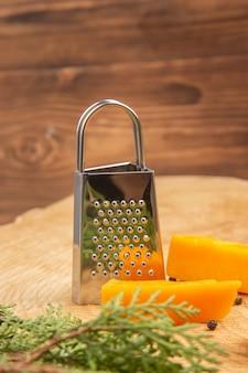 Vista frontale fette di formaggio sparse pepe nero grattugia pino ramo su superficie di legno