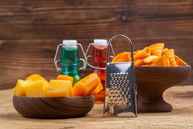 ボウルのチーズとチップスの正面図のスライスは、茶色の孤立した表面に赤と緑のボトルをおろします